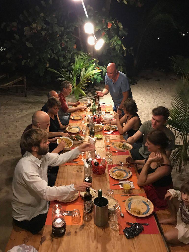 Abendessen in Mbuyu Beach. Alle Gäste sitzen unter dem Sternenhimmel an einem langen, gedeckten Tisch.