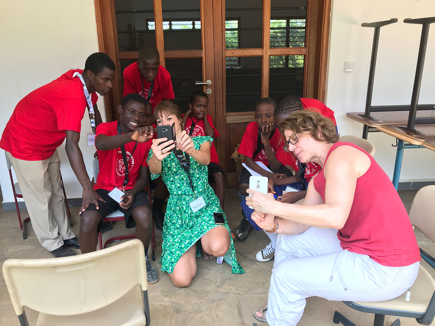 Maria showing three students and team leader Abdalla how to use a phone's camera. Melanie showing the same thing to two student on another phone.