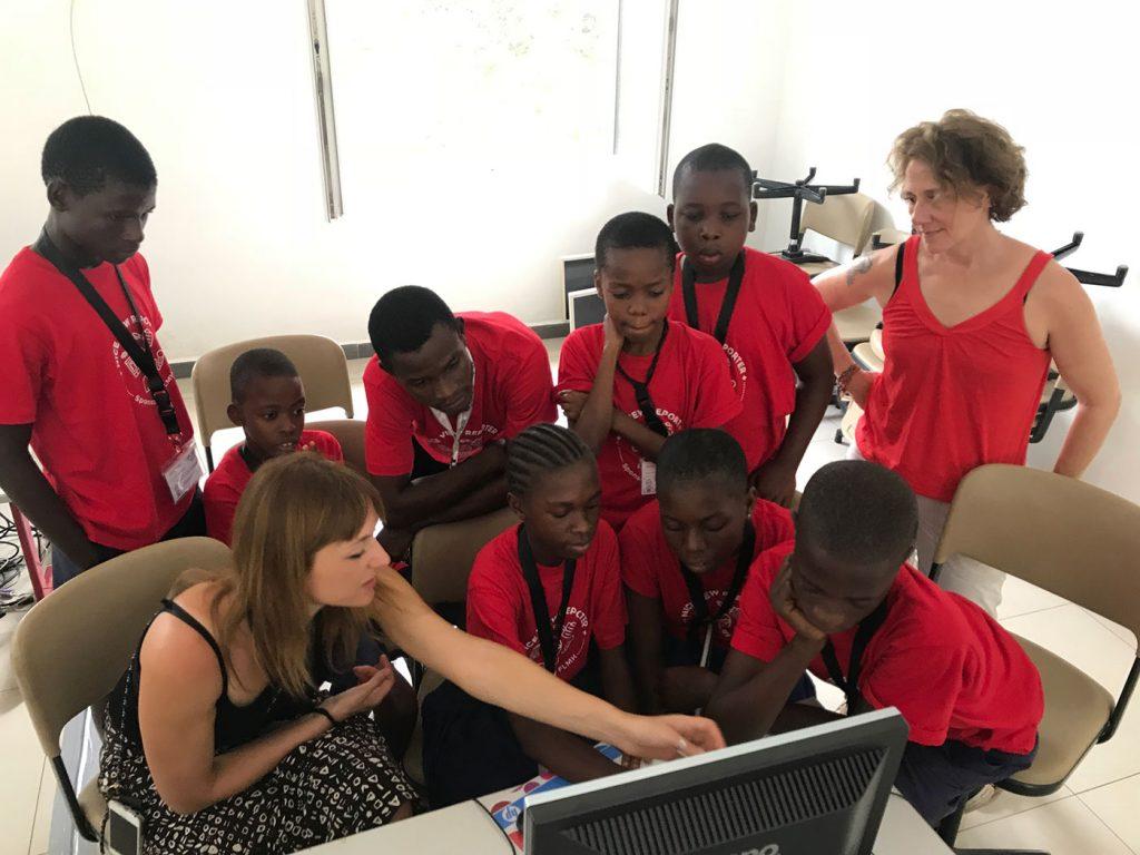 Sieben Schüler*innen und Teamleiter Abdallah sitzen im Computerraum. Maria und Melanie führen die Feinheiten der Bildbearbeitung vor.