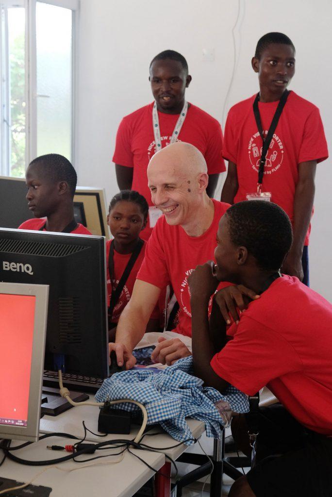 Bernhard sitzt im Kreise von fünf Schüler*innen des Teams Tim und erläutert die Funktionsweise von WordPress. Die Stimmung ist heiter.