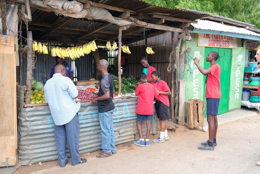 Vier Schüler*innen stehen an einem Marktstand in Msambweni und bereiten sich auf ihr Interview mit den Händlern vor. Einer der Schüler fotografiert den Stand.